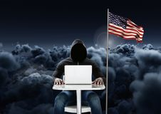 Hacker working on laptop close to the american flag with cloudy background. Digital composite of Hacker working on laptop close to the american flag with cloudy Stock Photography