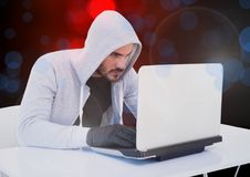 Hacker working on laptop with a digital background stock photo