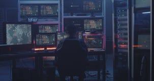 Hacker working with multiple monitors. Medium shot of a hacker working with multiple monitors stock video footage