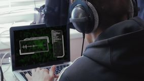 Man in headphones with sound chart. The hacker works on a computer with a sound chart and green binary symbols. The man in the headphones analyzes the voice code stock video