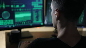 Hacker works at a computers and drink tea in a dark office room. Hacker works at computer with maps and data on display screens in a dark office room stock video