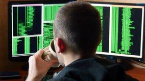 Hackera łamania kod i pić od filiżanki przy twój biurkiem Kryminalnego hackera sieci drążący system od jego zmroku Obrazy Royalty Free