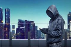 Hackera anonimowy używa smartphone zdjęcia royalty free