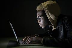 Hackera atak serwer w zmroku Afro hackera kilofa amerykański serwer od laptopu w ciemności zdjęcie royalty free