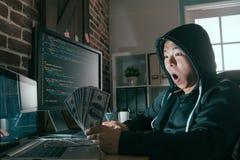 Hackera zdziwiony patrzeje gotówkowy banknot Zdjęcia Stock
