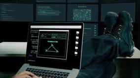 Hackerfüße bis zur Tabelle Hacker mit der Laptopkodierungsheldentat, zum des Codes zu knacken Mann in den Militärschuhen sitzt un stock footage