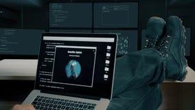 Hackerfüße bis zur Tabelle Hacker mit der Laptopkodierungsheldentat, zum des Codes zu knacken Spurkontakt und Satelitte, die durc stock video footage