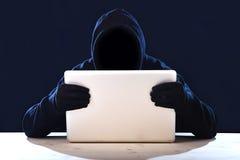 Hackermann in der schwarzen Haube und Maske mit dem Computerlaptop, der System im digitalen Eindringling Cyber-Verbrechenkonzept  Stockfotografie