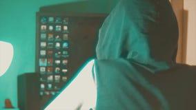 Hackermannprogrammierer in der Haube unter Verwendung des Computers zu Kerbeninformation und -daten vom Benutzerkonto Knickenteno stock footage