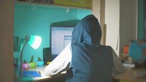 Hackermannprogrammierer in der Haube unter Verwendung des Computers zu Kerbeninformation und -daten vom Benutzerkonto orange Farb stock footage