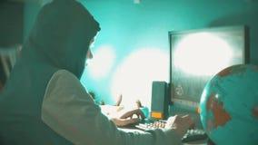 Hackermannprogrammierer in der Haube unter Verwendung des Computers zu Kerbeninformation und -daten vom Benutzerkonto orange Netz stock video footage