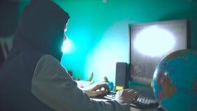 Hackermannprogrammierer in der Haube unter Verwendung des Computers zu Kerbeninformation und -daten vom Benutzerkonto zuhause onl stock video footage