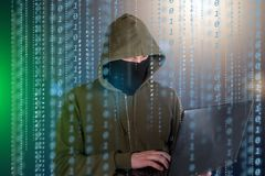 Hackers programmer look on screen and writes the program code hack information and user account.  Royalty Free Stock Photo