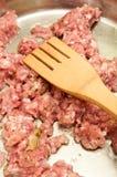 Hackfleisch im Heißöl in einer Bratpfanne und in einem hölzernen Mischer Stockfotos