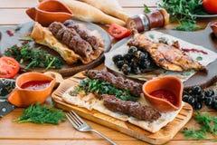 Hackfleisch Lyulya-Kebab mit Frischgemüse und Soßen auf einer Umhüllungstabelle Traditionelles georgisches Abendessen Stockfotos