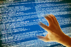 Hacking code. Hand grabbing a software code, hacking and computer crime concept Stock Image