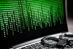 Hacking concept. Handcuffs on laptop Stock Image