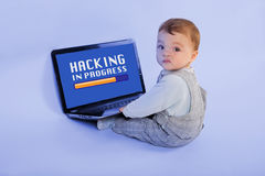 Hacking in progress by a baby. Funny image about the younges hacker in the world - Adorable baby sitting in front of the laptop and hacking stock image
