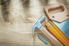 Hacksaw μετρητών σφυριών νυχιών ξύλινα ανοξείδωτα καρφιά στον ξύλινο πίνακα γ Στοκ φωτογραφίες με δικαίωμα ελεύθερης χρήσης