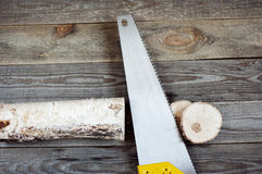 Hacksaw with a log. On a wooden background Royalty Free Stock Photos