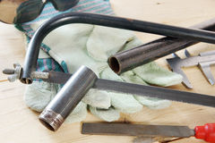Hacksaw and metal pipe on the wooden workbench Royalty Free Stock Image