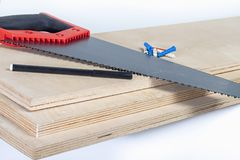 Hacksaw on plywood boards with colored dowels Stock Photography