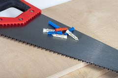 Hacksaw on plywood boards with dowels Royalty Free Stock Photo