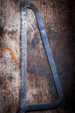 Hacksaw on wooden plank Royalty Free Stock Images