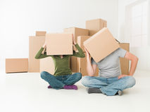 We had to make mortgage to afford this hous. Couple with boxes on their heads sitting on floor in their new house, feeling stressed Royalty Free Stock Photo