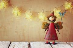 Hada linda en la tabla de madera delante de la guirnalda de las estrellas con el fondo de la luz del oro Foto de archivo