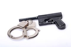 Hadcuffs and gun Royalty Free Stock Images