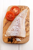 Haddock fillet on a wooden board Royalty Free Stock Photo