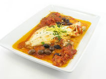 Haddock in a red sauce. On a white plate isolated  on white Stock Photo