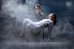 Hades & Persephone: To the Underworld. Dark haired men dressed all in black standing in pale, still lake water carrying a young maiden in white dress in a Royalty Free Stock Image