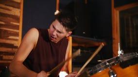 Hadnsome dobosz z mokrym włosy aktywnie bawić się muzykę w studiu w garażu swobodny ruch zdjęcie wideo