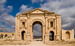 Hadrian\'s Arch. In the ancient roman town Jerash in Jordan. Built AD 129 to honour the visiting emperor. Sunny light, nice contrast of clouds and blue sky in Royalty Free Stock Photo