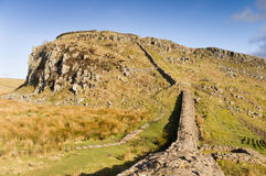 Hadrians Wall climbs Steel Rigg. Hadrians Wall ascends the Whin Sill at Steel Rigg Stock Photo