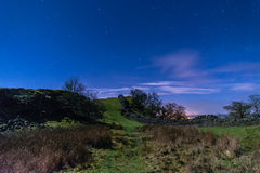 Hadrians Wall in a valley at night. Moonlit Hadrians Wall is in the recently awarded Dark Sky Park in Northumberland Royalty Free Stock Images