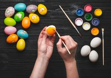 Hads painting eggs for Easter holiday on wooden table Stock Photos