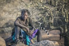 Free Hadza Man In Animal Skins Resting On A Rock Stock Photo - 158587010