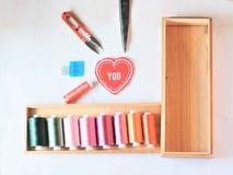 Hafciarscy nici i szyć narzędzia w drewna pudełku ustawiają na białej tkaninie Zdjęcia Stock