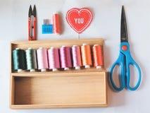 Hafciarscy nici i szyć narzędzia w drewna pudełku ustawiają na białej tkaninie Zdjęcia Royalty Free