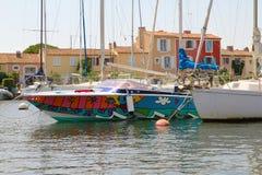 HAFEN GRIMAUD, FRANKREICH, AM 28. AUGUST 2015: Regenbogen färbte Boot im Hafen, mit traditionellen Provencal-Häusern Stockfotografie