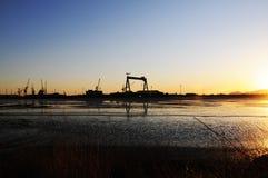 Hafen-Kräne, Seeküsten-Sonnenuntergang, Fracht und Schifffahrten Lizenzfreie Stockfotografie