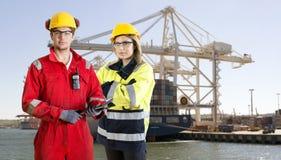Hafenarbeiter, die vor einem Containerschiff aufwerfen Stockfotos