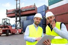 Hafenarbeiter und Aufsichtskraft, die Behälterdaten überprüfen Stockbild