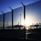 Hafengebietzaun mit Schattenbildern von Kränen Stockfotos