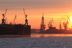 Hafenkräne bei Sonnenuntergang Stockbilder