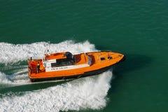 Hafenlotse auf dem kleinen Schiff, das an der hohen Geschwindigkeit sich bewegt Kleiner orange Bootsversand auf Meerwasser Versuc Lizenzfreie Stockfotos