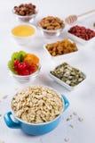 Hafer blättert in der blauen Schüssel und in den verschiedenen köstlichen Bestandteilen zum gesundes Frühstück auf dem Küchentisc Stockfotos